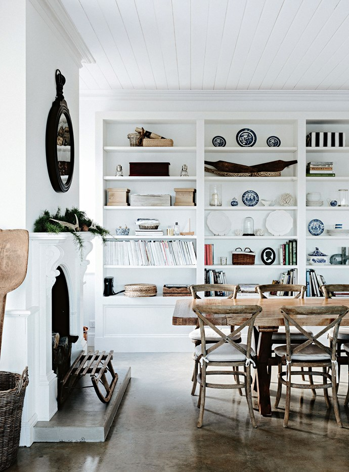 """The dining room features custom-made shelves and the original mantelpiece and timber ceilings. The dining table is from Dare Gallery. """"For about six months we filled our garage up with furniture and got a truck to take it down to Tassie,"""" says Lucy. Under the fireplace sits an antique toboggan."""