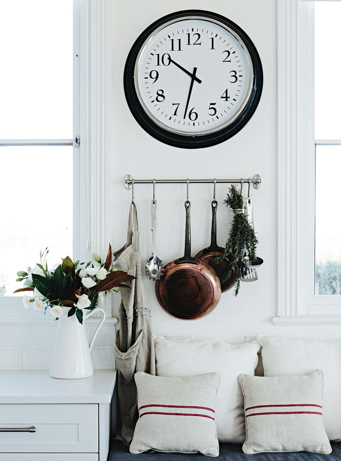 """The window seat in the kitchen under a wall clock from [IKEA](https://fave.co/2OVDmrL target=""""_blank"""" rel=""""nofollow"""")."""