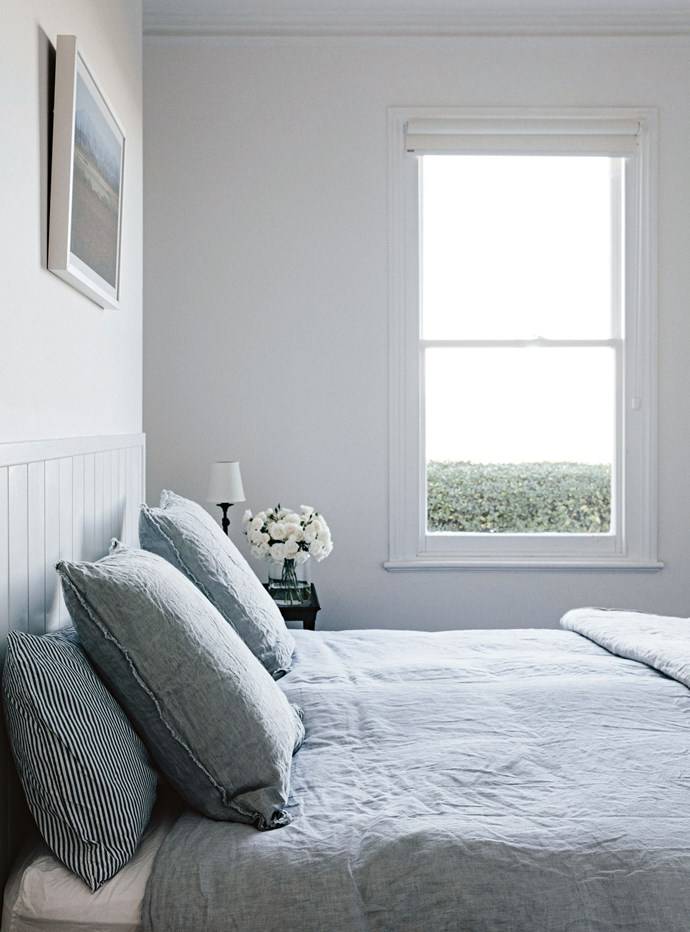 """The linen in the main bedroom is from [Hale Mercantile Co](https://halemercantilecolinen.com/ target=""""_blank"""" rel=""""nofollow""""), while the bedside lamp is from Pottery Barn. Lining boards cover an old fireplace to make a bedhead, with one of Stewart's framed landscape photographs above. """"In the morning you look out and just see green and hear the sheep out the window,"""" says Lucy."""
