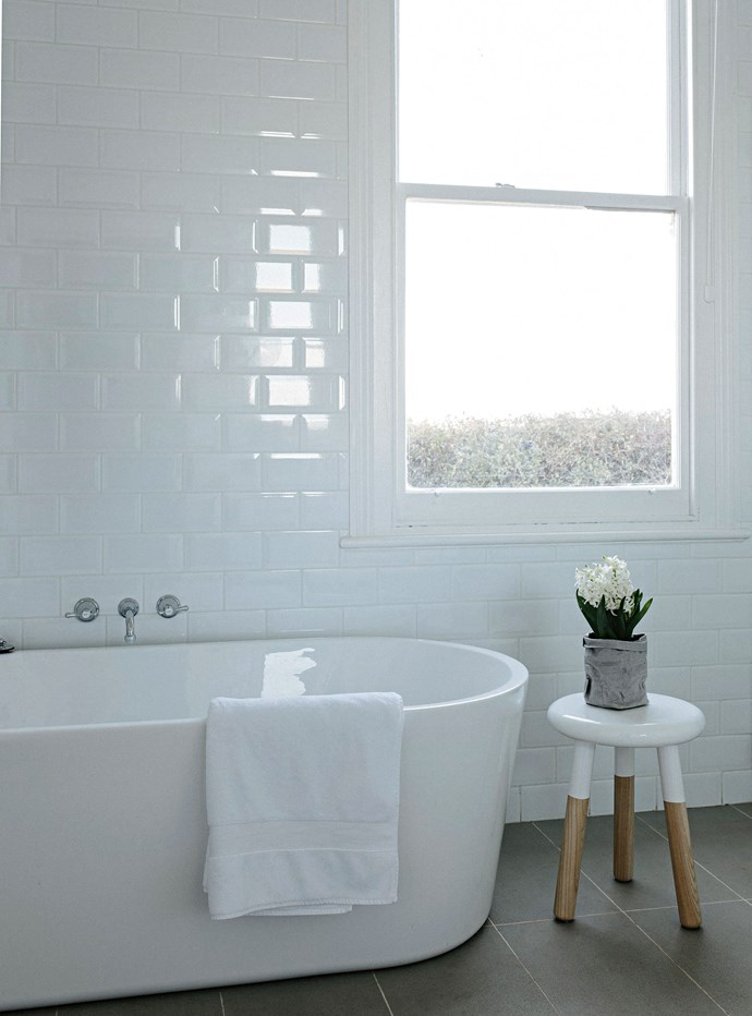 """The bathroom features a deep bath with tapware from Restoration Hardware in New York. The 'Malmo' stool is from [Schots Home Emporium](https://www.schots.com.au/ target=""""_blank"""" rel=""""nofollow"""")."""