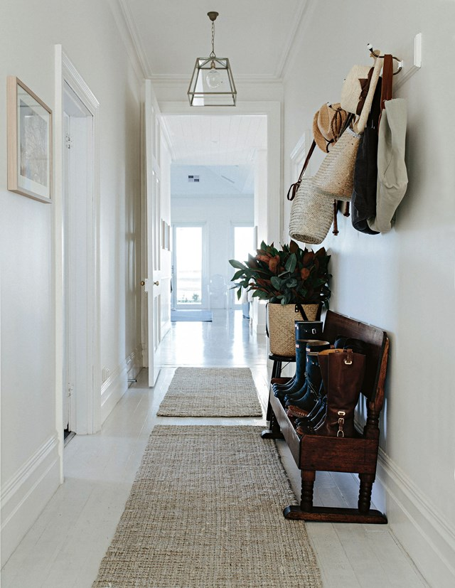 "An antique church pew adds warmth to the all-white hallway of a [restored farmhouse in Tasmania](https://www.homestolove.com.au/farmstay-tasmania-12425|target=""_blank""). It provides plenty of space for the family's line-up of gumboots that they regularly don to walk around the farm picking produce."
