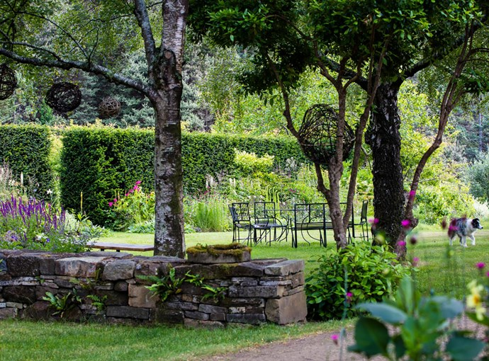 Sally built this drystone wall from 'collected' stone she salvaged locally; spherical wire sculptures hang from the trees, adding a whimsical touch to this pretty sitting area.
