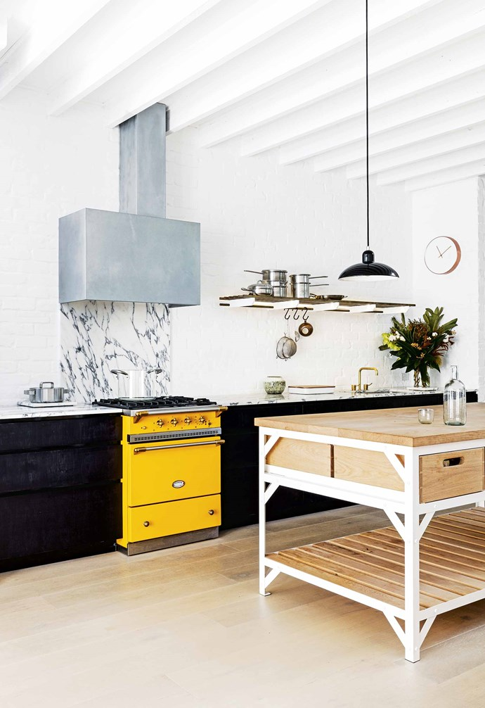 """**Here comes the sun** In this kitchen, the moody hues of the black custom cabinetry are punctuated by a sunny yellow Lacanche 'Cormatin' cooker from Malcolm St James. *Project builder: [PMD Build](http://pmdbuild.com.au/