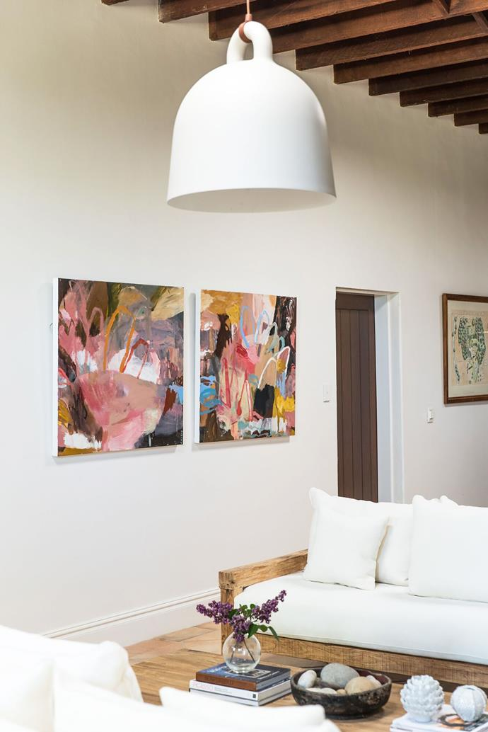 In the living room, a white palette allows the collection of vibrant art to be the focal point.