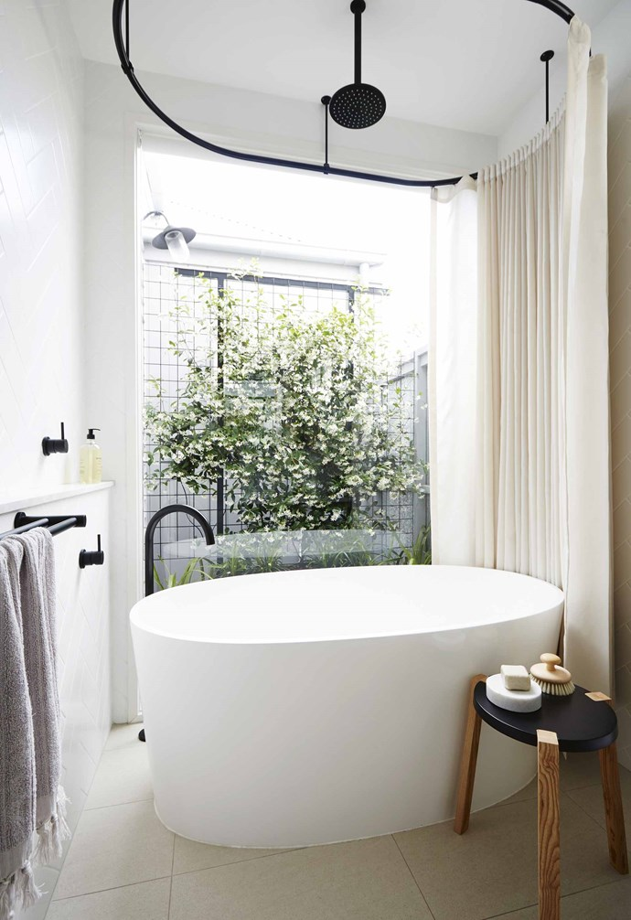 "The back wall of black steel-framed windows and doors was the couple's idea. ""We had done a lot of research,"" says Rachael. ""We drew the doors and took photos to show Terri what we wanted. It was all about bringing black into the scheme and playing up the green in the garden.""<br><br>**Bathroom** The success of this home is due to smart use of space and refined details. The bathroom is a great example with a tub in front of a private courtyard for a day spa feel and black [Astra Walker](http://www.astrawalker.com.au/