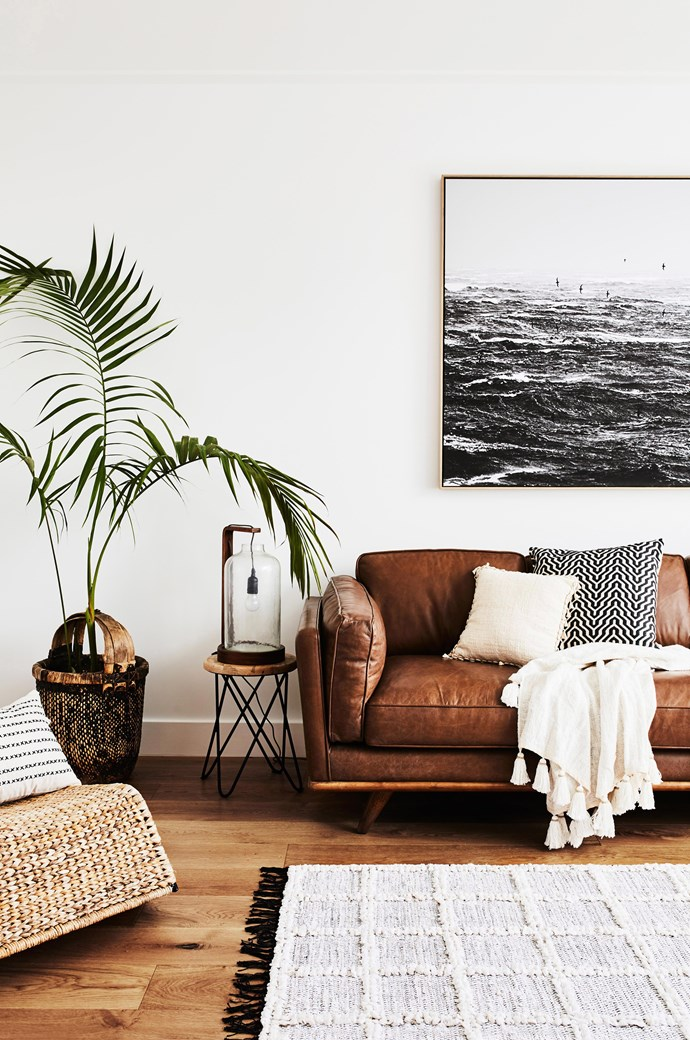"""A soft leather couch, wool rug, chunky throw and touches of timber add warmth and texture to this [living room](https://www.homestolove.com.au/how-to-decorate-your-living-room-3911