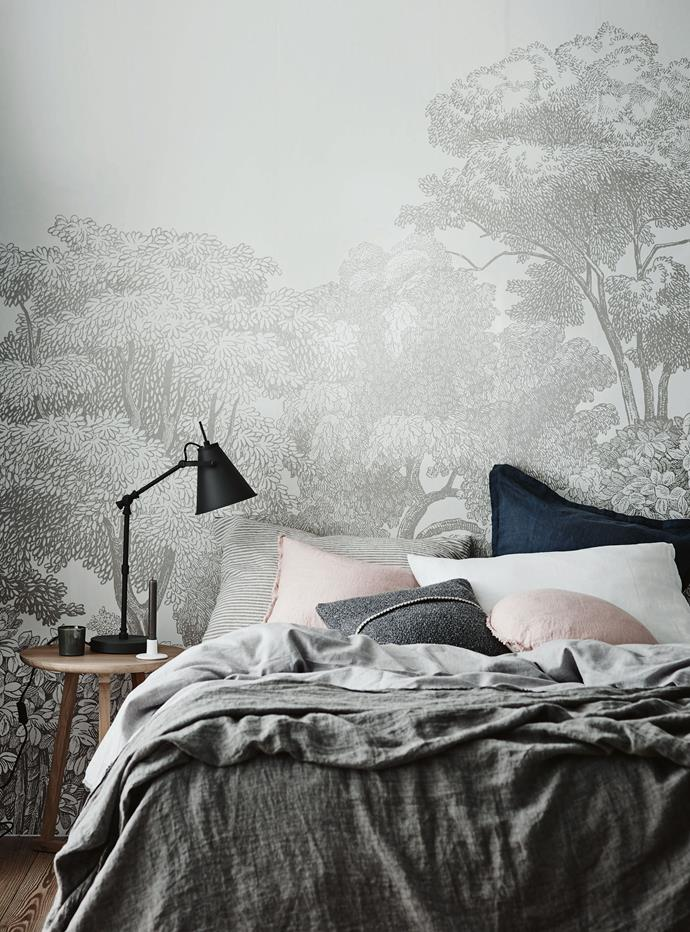 Wallpaper can work wonders when it comes to transforming your bedroom into a warm and whimsical escape. Here, a forest landscape in soft grey tones ties in perfectly with the bedlinen and furnishings, creating a space made for rest and relaxation.