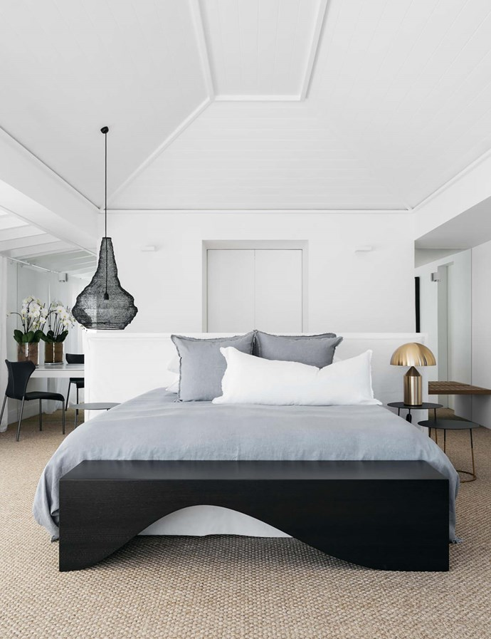 An 'Atollo' table lamp sits on a 'Nimbus II 40' bedside table in the main bedroom. Hale Mercantile Co. bed linen. B&B Italia 'Papilio' black leather chair from Space. Black wire crochet suspension light from Les Interieurs.