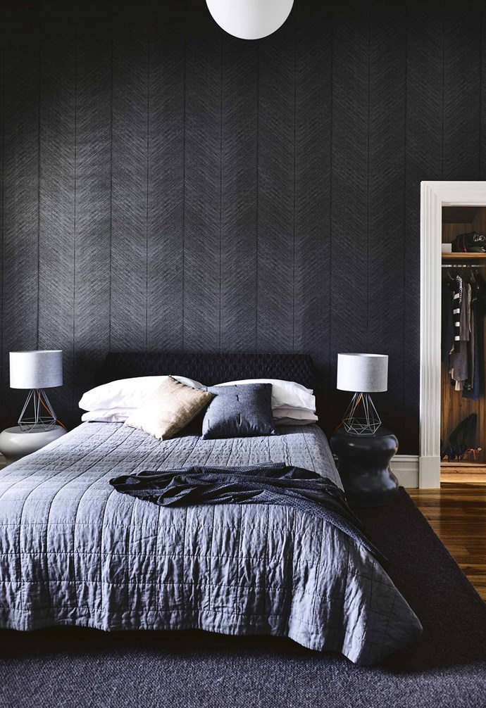 """**Dark and moody** The textured 'Quill' wallpaper in Ebony from [Porter's Paints](https://www.porterspaints.com/ target=""""_blank"""" rel=""""nofollow"""") is paired with a plush textured bedhead, a charcoal rug and a deep grey quilt, adding a multi-tonal dark and moody element to the bedroom in this [contemporary home](https://www.homestolove.com.au/concrete-brick-and-timber-ideas-from-a-contemporary-home-17933 target=""""_blank""""). *Styling: Rachel Vigor   Photography: Derek Swalwell*."""