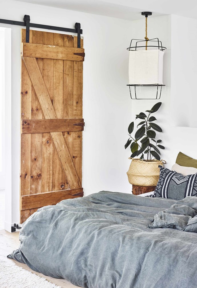"""**Door delight** A [Queensland pool house](https://www.homestolove.com.au/pool-house-19517 target=""""_blank"""") makes the most of its compact space with clever design choices. A rustic barn door becomes a design feature in the bedroom, as well as allowing for seamless connection between the ensuite and sleeping zone. *Styling: Hayley Jenkin   Photography: Toby Scott*."""