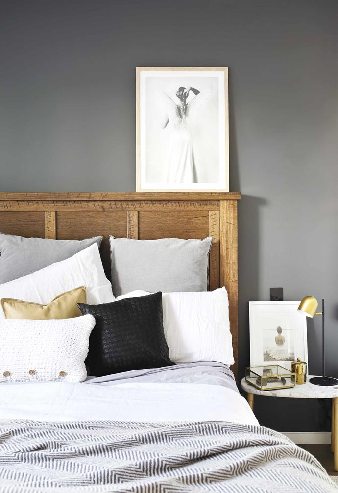 "**Greyscale** In this [Palm Springs-style home](https://www.homestolove.com.au/palm-springs-house-coorparoo-19769|target=""_blank"") grey walls create an intimate atmosphere in the master bedroom. A rustic timber bedhead is paired with a muted palette of greys and a hint of brass to create a contemporary look. *Styling: Simone Barter 