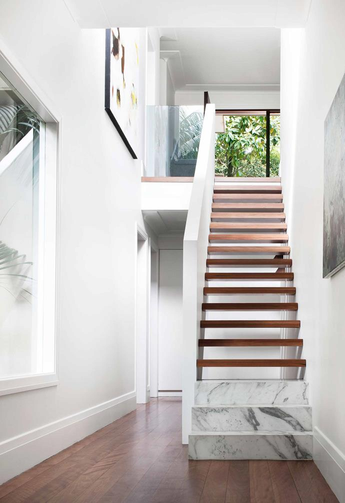 **Hallway** A striking staircase in the hallway showcases the luxe material palette used throughout the home, with Arabescato marble from [Granite & Marble](http://granitemarbleworks.com.au/) works paired with Brushbox flooring. The staircase features an artwork by Conchita Carambano to the left, and a piece by Emma Ward to the right. All walls, ceilings and trims are painted in [Dulux](https://www.dulux.com.au/) Natural White throughout the home.