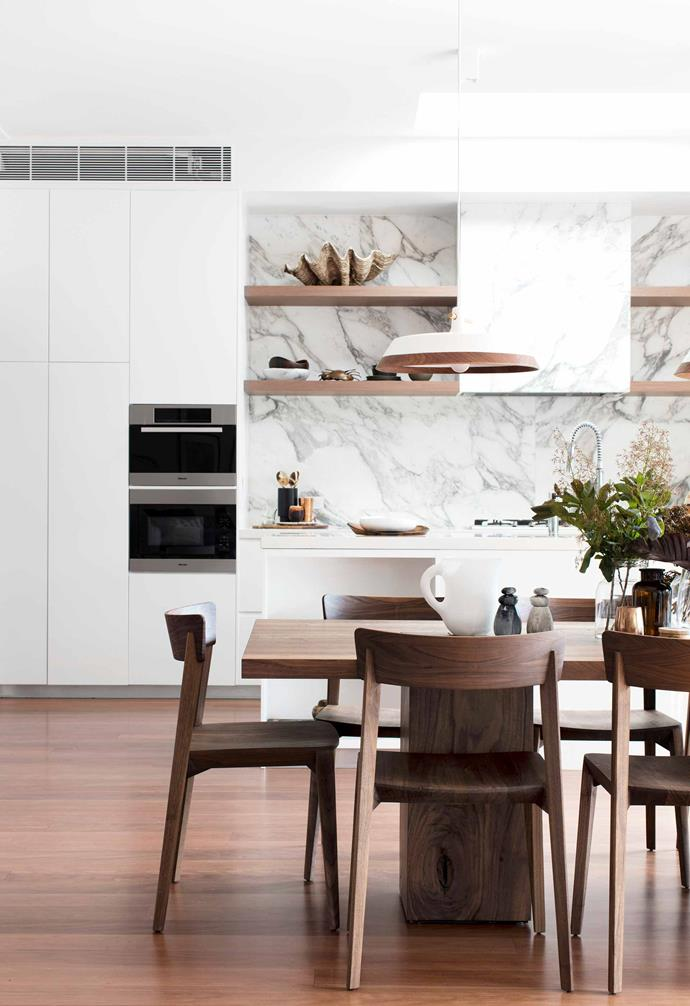 **Kitchen/dining** Melanie and Hamish wanted a robust eight-seater dining table that would accommodate their extended family and have substantial presence in the open-plan kitchen/dining area. The strong, sleek lines of the Boss dining table and Mia chairs, both from [Fanuli](https://www.fanuli.com.au/), are balanced by the organic grain of the kitchen's Arabescato marble splashback. The KAV Classic ceramic and walnut pendant light over the dining table, from [ECC Lighting+Furniture](https://www.ecc.com.au/), visually links the kitchen's white joinery and stone-composite benchtops (both existing) with the timber elements.