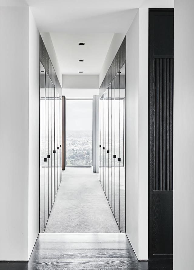"""The wardrobes in this [city apartment](https://www.homestolove.com.au/city-apartment-sleek-interiors-19780 target=""""_blank"""") designed by Kimberley-jade Bawden feature smoked glass doors with European oak panelling which create an ultra-sleek aesthetic. *Photograph*: Lisa Cohen   *Styling*: Jack Milenkovic. From *Belle* February/March 2019."""