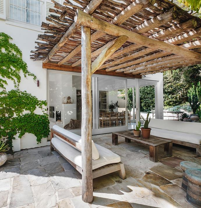 Latte-style stripped timber poles give the pergola beside the pool a rustic ambience, reinforced by the crazy paving and the *Euphorbia trigona* and *Agave parryi* in the terracotta pots.