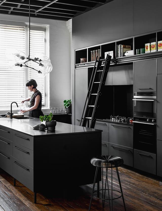 "An island bench in a beautiful Bengal Black honed granite is at the centre of this bold kitchen in a [warehouse conversion in Brisbane](https://www.homestolove.com.au/historic-warehouse-turned-industrial-apartment-19973|target=""_blank""). *Photograph*: Cathy Schulser 