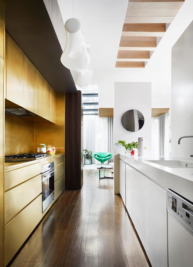 "Brass casts a warm glow over the rear cabinetry in the kitchen of this [renovated heritage cottage](https://www.homestolove.com.au/renovated-heritage-cottage-melbourne-19848|target=""_blank""). *Photograph*: Armelle Habib 