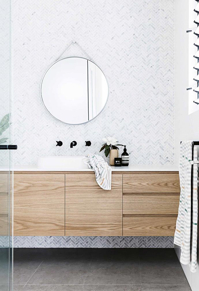 "Multi-toned small tiles are laid in a herringbone pattern to create a striking visual feature in the bathroom of this [family-friendly open plan home](https://www.homestolove.com.au/inside-an-open-plan-home-fit-for-a-growing-family-16969|target=""_blank""). *Design: [Stubbs Design Tribe](https://designtribeprojects.com.au/