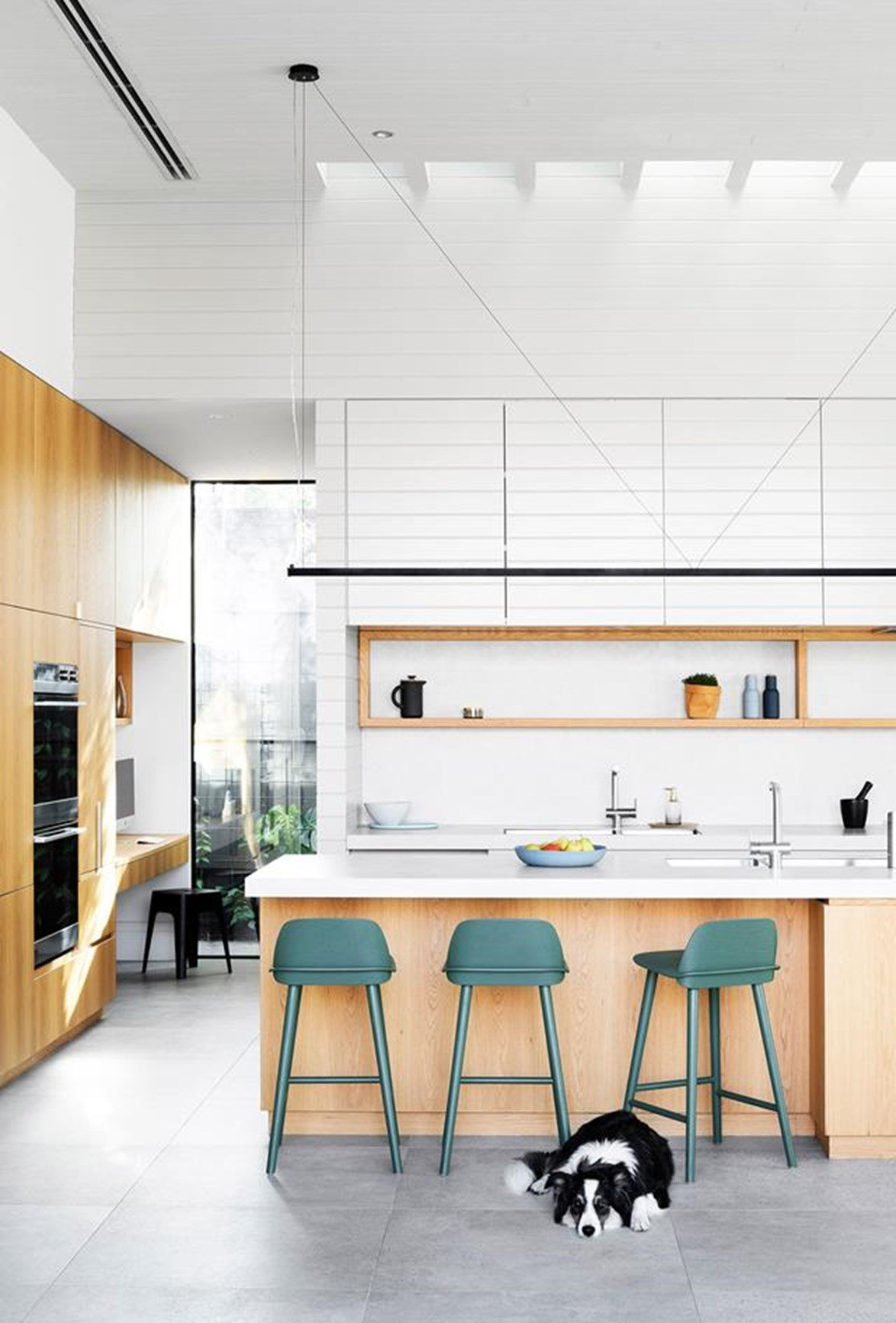 White porcelain surfaces, timber cabinetry and concrete floors are a winning combination in this fuss-free, family kitchen. Muuto 'Nerd' bar stools in a muted sage green add a welcomed pop of colour.
