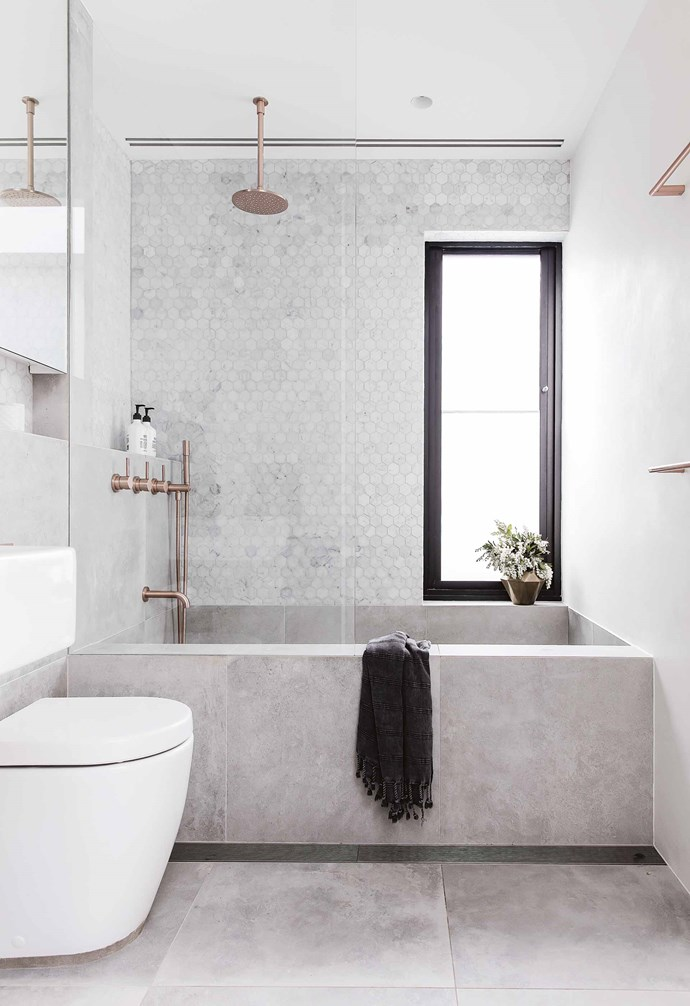 "A small but deep bath was built in the upstairs bathroom [of this renovated Queens Park cottage](https://www.homestolove.com.au/federation-cottage-queens-park-18311|target=""_blank"") using large format grey tiles. Rose-gold tapware adds warmth to the space. *Design: [Alexander&Co](https://alexanderand.co/