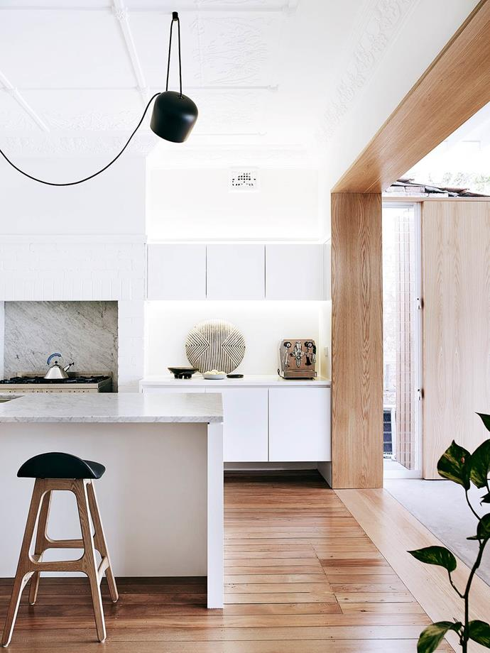"In this [modern kitchen](https://www.homestolove.com.au/modernism-inspires-laid-back-family-home-2762|target=""_blank""), shields and bowls the owners bought in Africa are earthy elements in the restrained palette. Benchtop and splashback in Carrara marble are from Milestone Building. Flos Aim pendant light from Euroluce. Erik Buch bar stools from Great Dane Furniture. *Photograph*: Prue Ruscoe 
