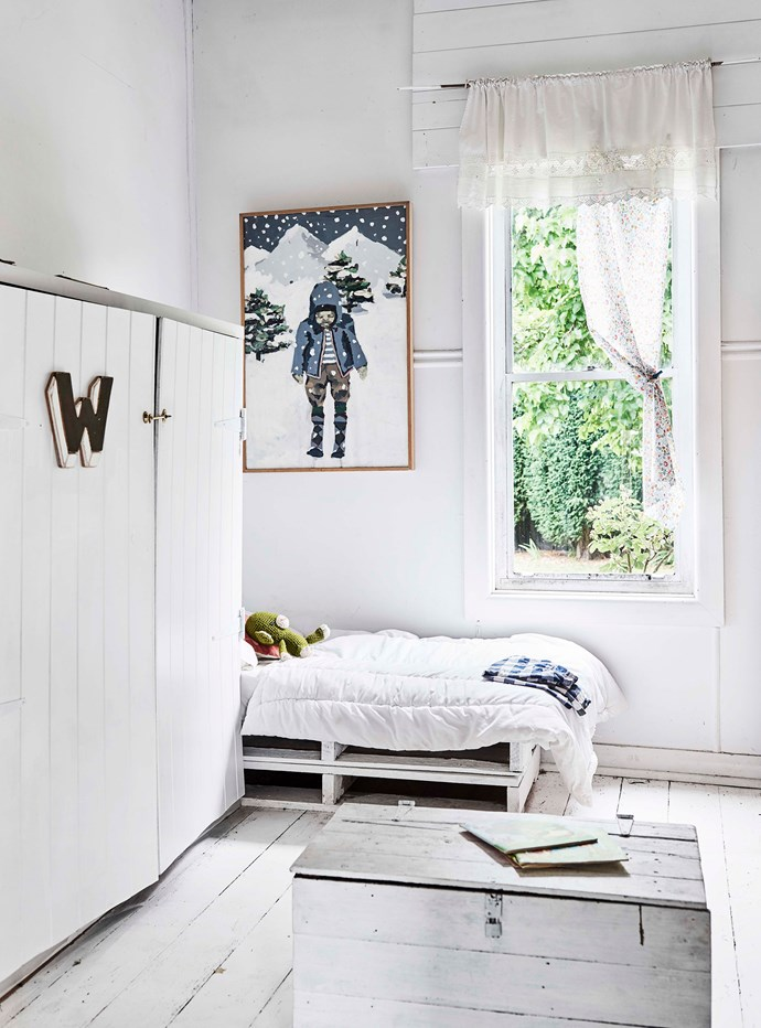 "Wilbur's Dream 2014 hangs above the bed in Wilbur's all-white bedroom. Zoe's creative approach — that sees an old hardback copy of The Reader's Digest Complete Atlas of Australia serve as a painter's palette — has also helped with the home's steady restoration, which is still a work in progress. One of Zoe's future plans for the cottage involves designing wallpaper. ""I'd really love to make my own for some of the rooms."""