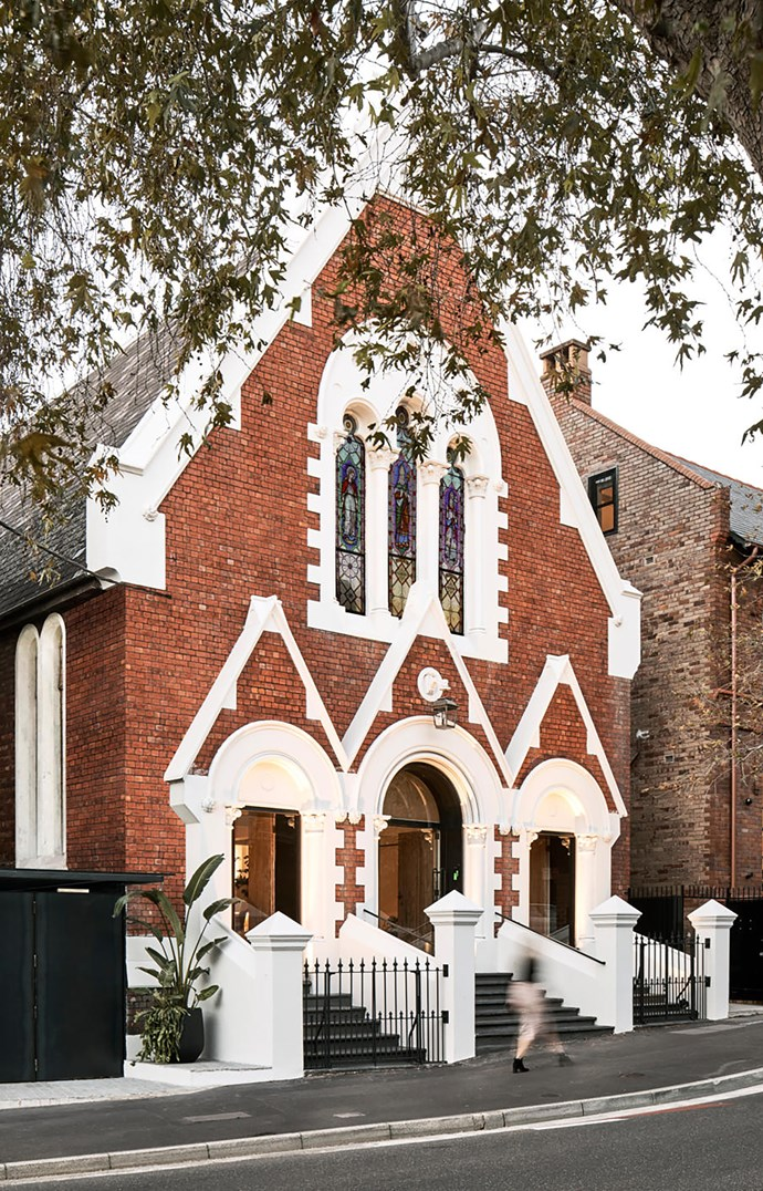 The restored Gothic church facade with new raw steel and glass arched openings.