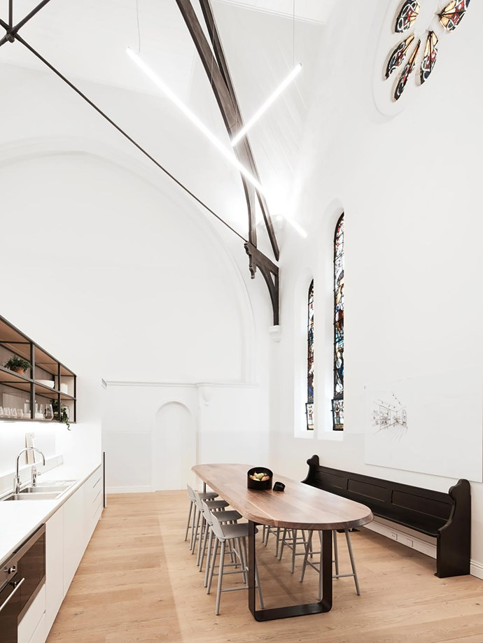 Breakout space featuring a custom table by Squillace, a restored original pew and bespoke kitchen joinery built by specialist building company Élan.