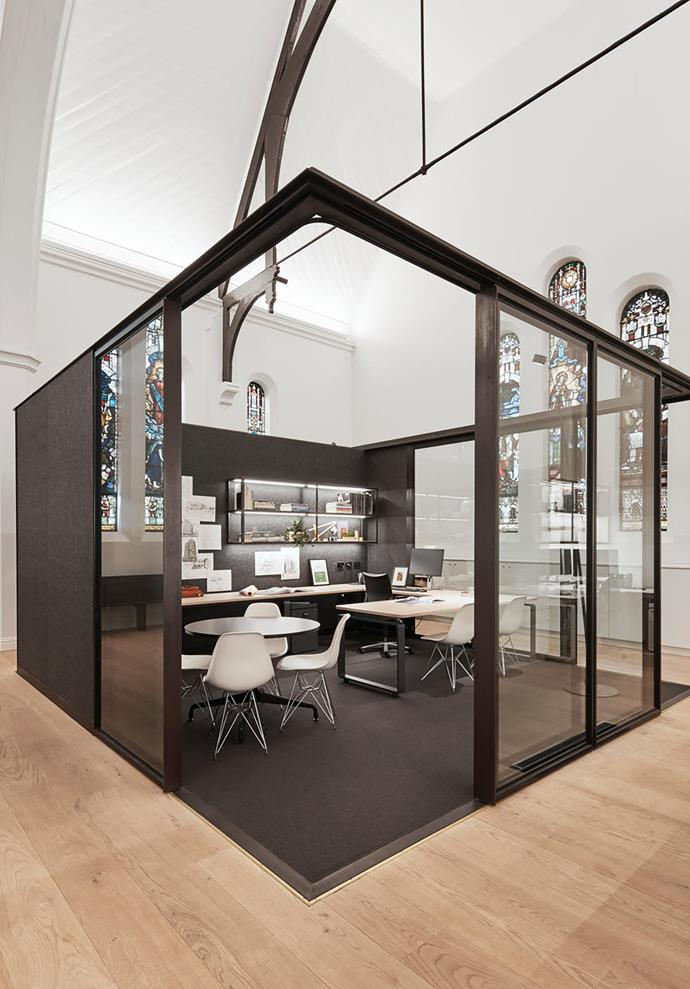 The steel and glass-framed office inset from the original church walls.