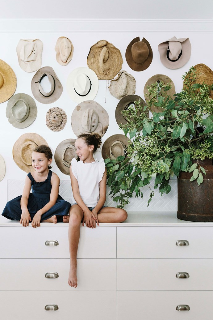 Annabel and Matilda McDonald in front of a collection of work hats in the laundry at their family's Goondiwindi farmhouse.