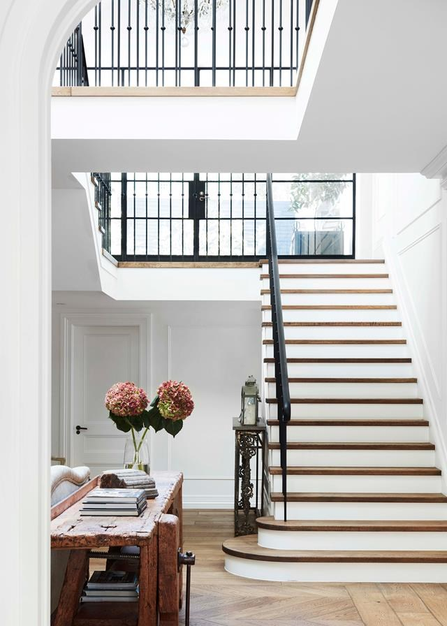 """With its juxtaposition of modern and traditional – a flowing wrought-iron balustrade and classic wall panelling teamed with industrial steel-framed windows and skylight – [this entryway](https://www.homestolove.com.au/gothic-revival-home-19307
