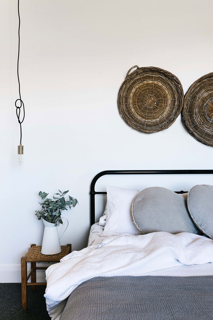 """Woven baskets adorn the wall in the bedroom. Josh's mum made the rattan stool beside the bed, dressed with bedding from [I Love Linen](https://www.ilovelinen.com.au/