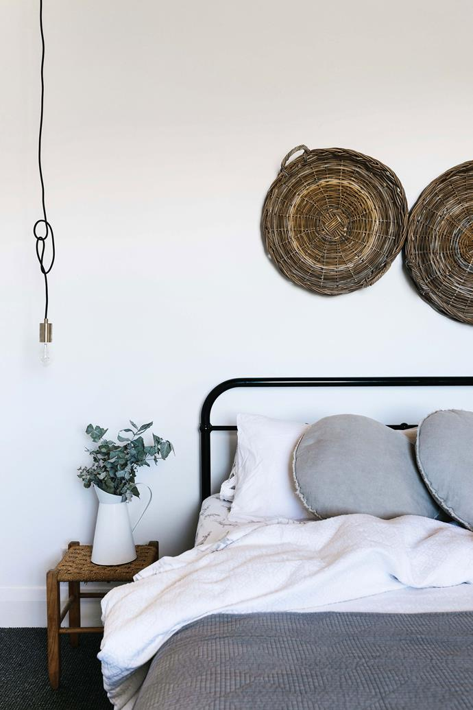 """Woven baskets adorn the wall in the bedroom. Josh's mum made the rattan stool beside the bed, dressed with bedding from [I Love Linen](https://www.ilovelinen.com.au/ target=""""_blank"""" rel=""""nofollow"""")."""