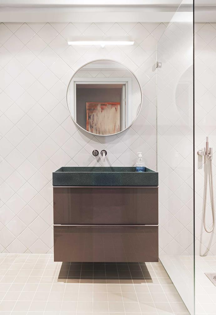 """**Bathroom** Despite looking white at first glance, the bathroom is actually light grey and green, with a generous Corian sink. """"It's big so the kids can splash around in it all they want,"""" says Daniel. Reflected in the mirror is the family's evolving art piece."""