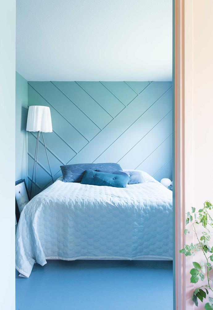 """**Master bedroom** Watery greens and blues make this sleeping space ultra relaxing. The bedding and cushions are from [Hay](https://hayshop.com.au/ target=""""_blank"""" rel=""""nofollow""""). Daniel created a backdrop for his bed by gluing wooden strips to the wall in a diagonal pattern and painting over them. He used the same technique in his living area to make the dado rail."""