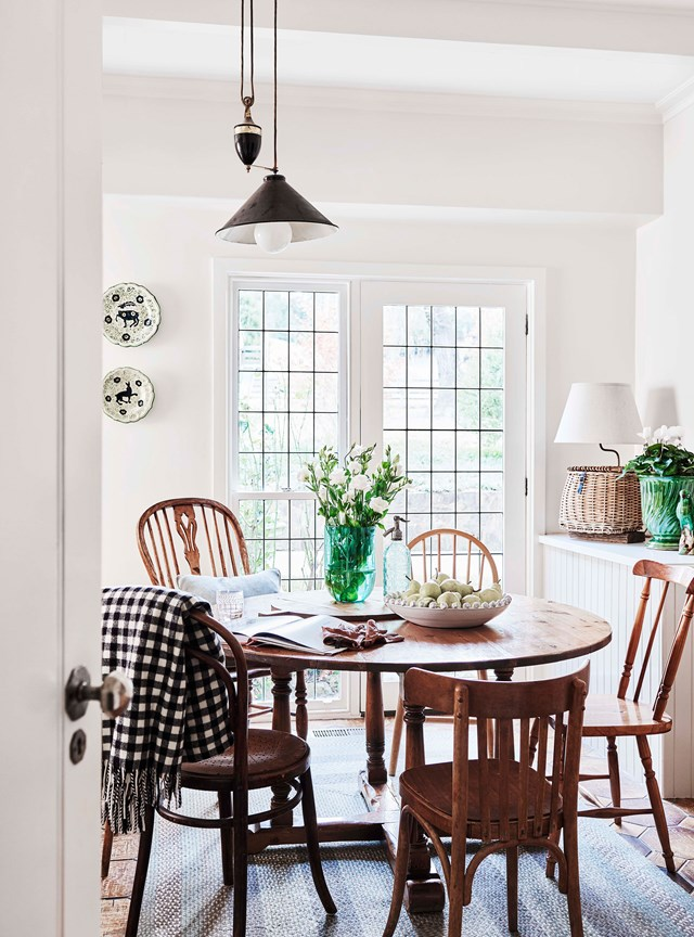 The kitchen adjoins a cosy dining room styled with a round timber table, adjustable vintage pendant light and a pair of French doors.