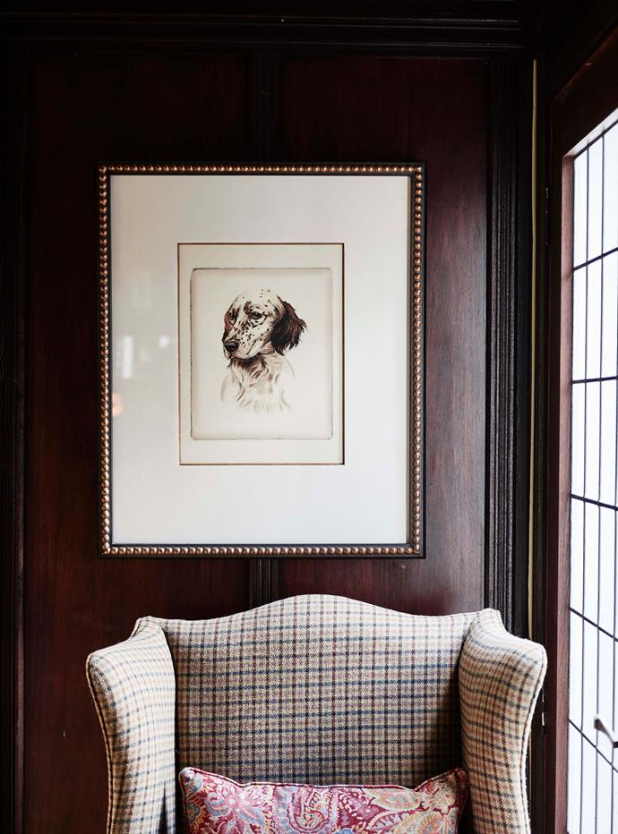 A Ralph Lauren print hangs above a plaid armchair.