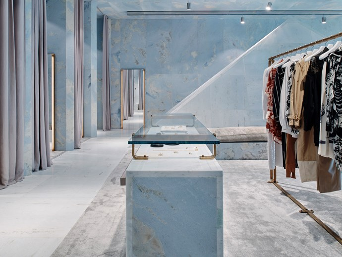 Floor-to-ceiling changing room curtains, large rugs and cushioned benches bring tactility to the marble, which is accented with chrome steel and bronze.