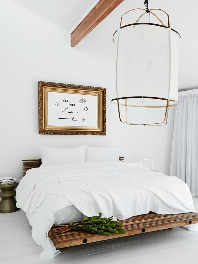 Timber and metallic accents add texture and warmth to this breezy, all-white bedroom while complementing the minimalist aesthetic. A large lantern-style light by Ay Illuminate makes good use of the high ceilings.