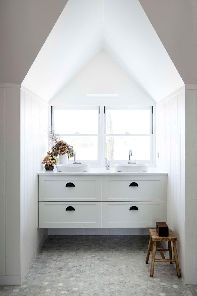Mosaic Carrara marble floor tiles from Surface Gallery add a modern feel to the bathroom.