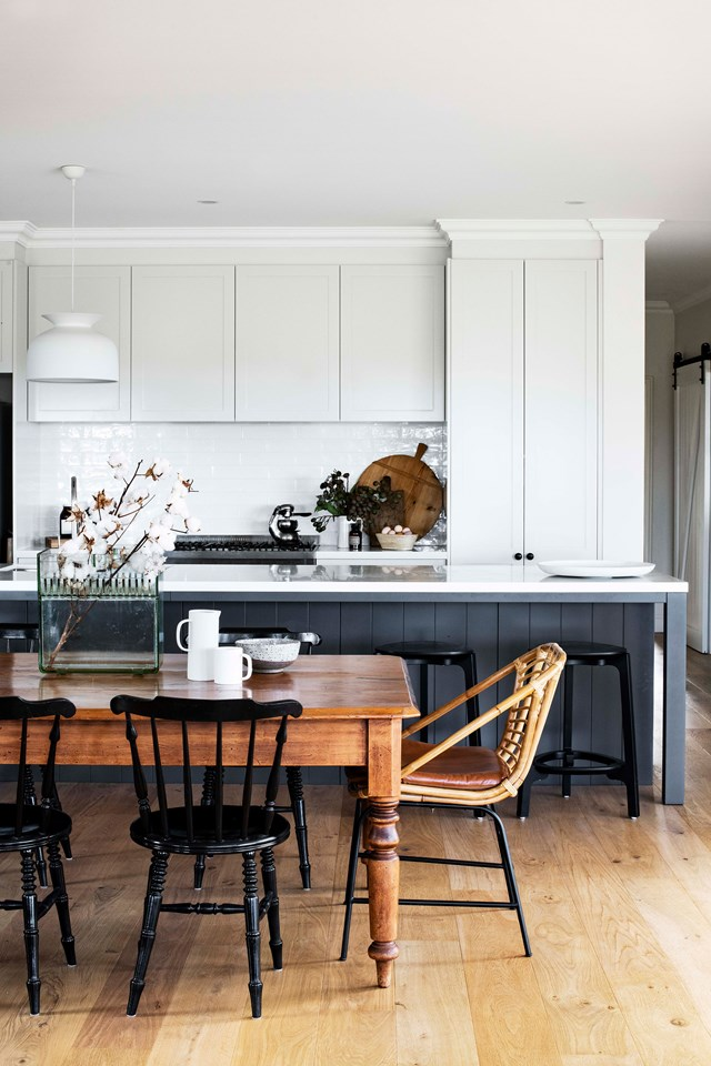 Timeless and sophisticated, this monochrome kitchen ties in with the rest of this renovated schoolmaster's house in Milton, NSW. An antique timber dining table adds character and warmth, while modern pendants and black accents keep things contemporary.