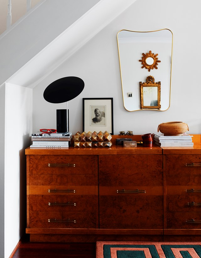 "A beautiful timber console from The Vault Sydney fits perfectly under the stairs in Phoebe Nicol's home. ""All my fabrics and samples are tucked away in here,"" Phoebe says. The brass mirror hanging above is by Gubi."