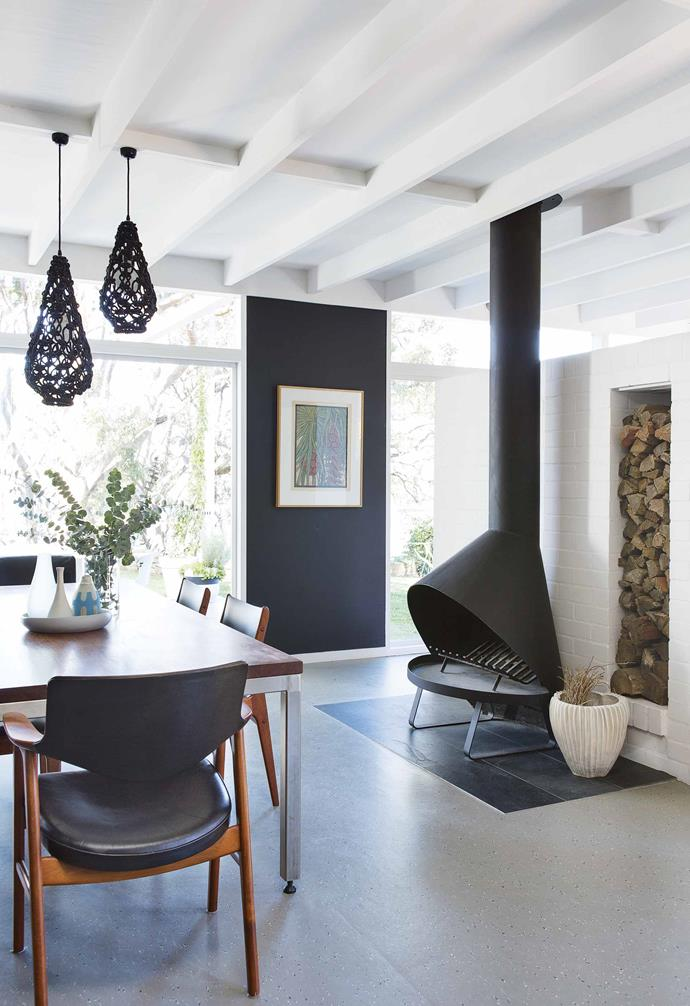 "This [modernist home](https://www.homestolove.com.au/step-inside-this-colourful-and-practical-family-home-17570|target=""_blank"") features dark walls throughout the open-plan kitchen and living area, adding dramatic contrast to the ample natural light. *Styling: Kerrie-Ann Jones 