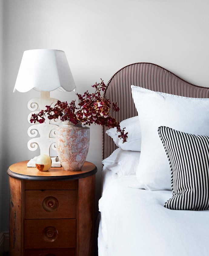Phoebe custom made the upholstered bedhead with cushions to match. The Aptos Cruz vase, bedside table and lamp are all from The Vault Sydney.