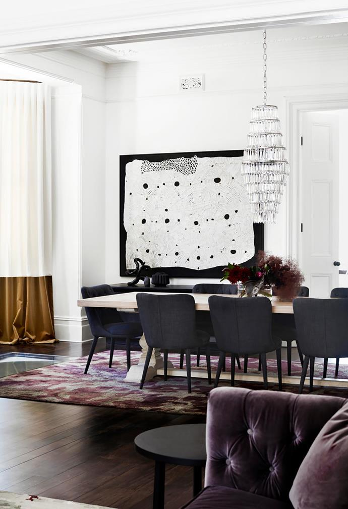 The dining area has a table from MCM House and chairs from Coco Republic on a rug designed by Suzanne Gorman and made by Tappeti. Waterford Crystal 'Etoile' pendant light from Cult. Curtains in ivory linen and gold velvet from Zepel Fabrics. Artwork is by Doris Bush Nungarrayi.