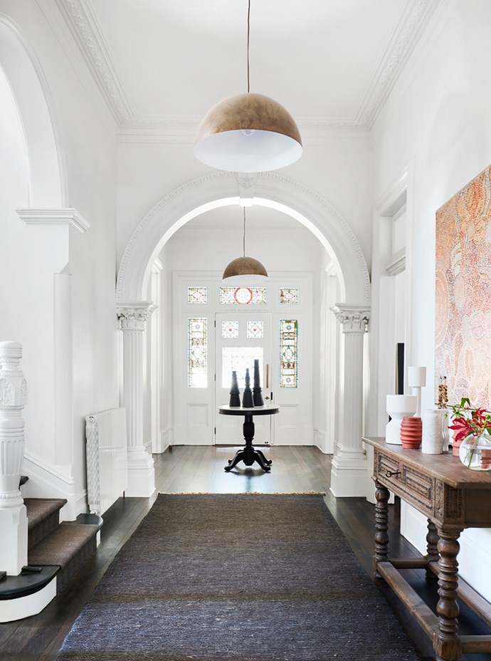 The expansive entrance hall has a rug from Armadillo & Co. Round table from Pottery Barn. Ralph Lauren sideboard from The Country Trader with an artwork by Nellie Ngampa Coulthard above.