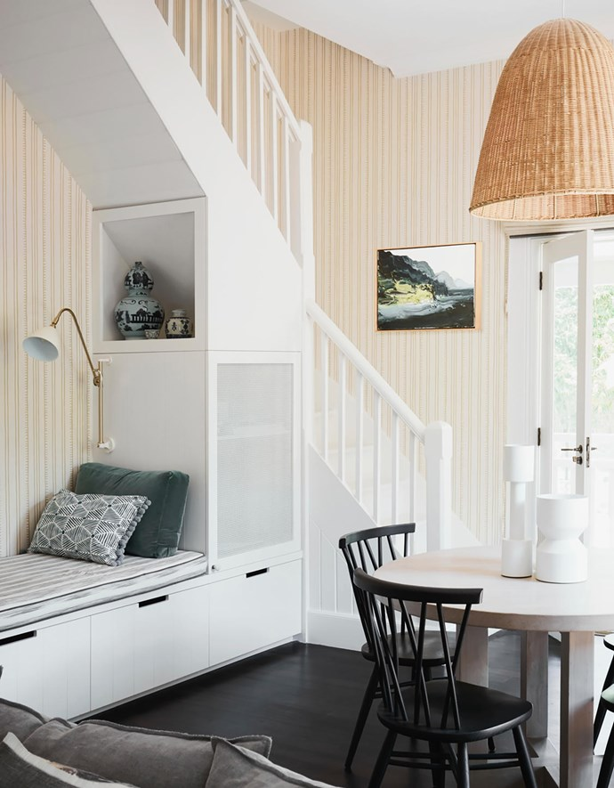In the family room, Ercol 'Chiltern' chairs from Temperature Design surround a table from MCM House. Pendant light from The Family Love Tree. Artwork by Paul Ryan. Wallpaper by Anna Spiro from Porter's Paints. The maid's staircase has been closed off at the top but was kept as a folly.