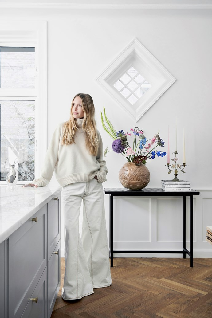 """""""The first time I set foot in this house, I immediately sensed the good energy,"""" Pernille says. On a green-tiled table from Warm Nordic she's placed a large Missoni vase and vintage candleholder from Fil De Fer."""