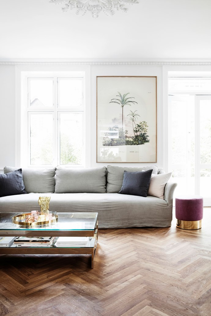 """Pernille defines her style as """"minimalist, classic with a mix of materials"""". Here, a grey linen sofa from Studio Oliver Gustav sits alongside a purple velvet stool from The Apartment. The glass and brass coffee table is from Dusty Deco and the framed palm tree poster is from Beau Marché."""