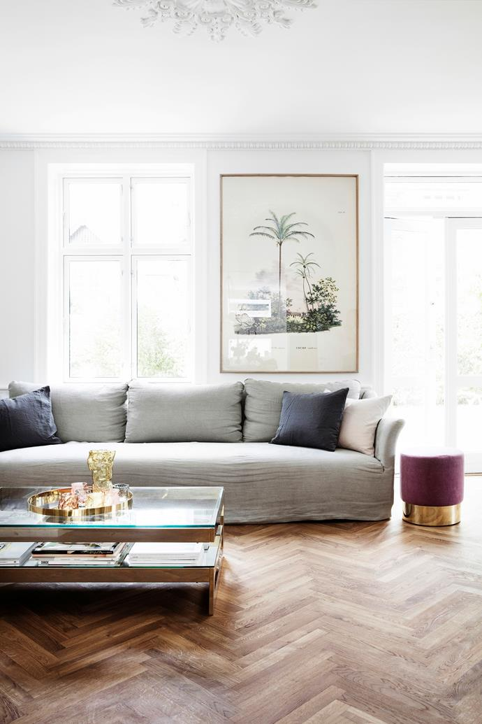 "Pernille defines her style as ""minimalist, classic with a mix of materials"". Here, a grey linen sofa from Studio Oliver Gustav sits alongside a purple velvet stool from The Apartment. The glass and brass coffee table is from Dusty Deco and the framed palm tree poster is from Beau Marché."